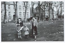 Einschulung April 1937. Der 1. Schultag. Ein Junge mit Schultüte/Zückertüte steht mit Geschwistern, Mutter und Großmutter auf dem Schloßplatz vor der Friedrich-Ebert-Schule, derzeit (1937) genannt