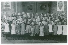 Schloßplatzschule (Friedrich-Ebert-Schule). Mädchenklasse mit Lehrerin vor der Eingangstür der Schule. An der Hauswand sieht man Plakate mit dem Aufruf zur Kriegsanleihe. Aufnahme 1917/18. 1. Weltkrieg. Repro.
